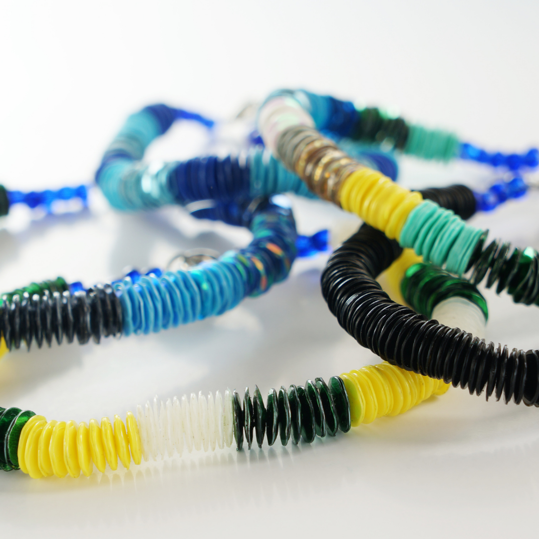 Handmade beaded bracelets on string in multiple colors including blue aquamarine yellow and green